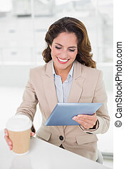 Happy businesswoman using digital tablet at her desk holding disposable cup in bright office
