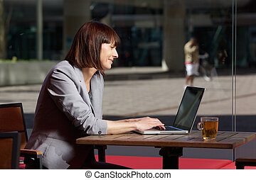 Happy businesswoman using laptop at cafe