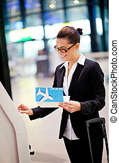 happy businesswoman using self help check in machine at ...