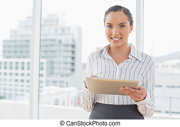 Happy businesswoman using tablet while looking at camera