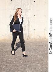 Happy businesswoman walking on the street