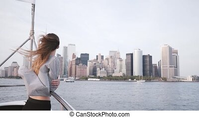 Happy businesswoman with hair blowing in the wind watching epic Manhattan skyline view in New York on a boat slow motion