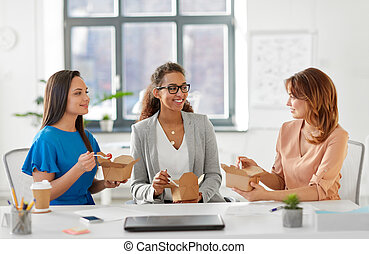 happy businesswomen eating take out food at office - ...