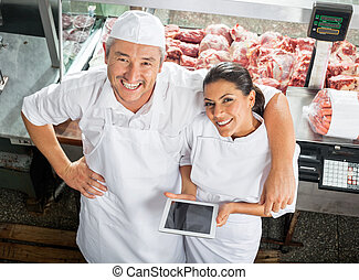 Happy Butchers With Digital Tablet In Butchery