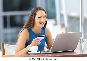 Happy buyer holding a credit card looking at you