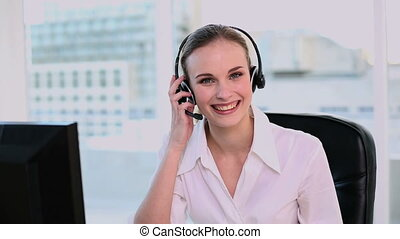 Happy call center agent working in her office