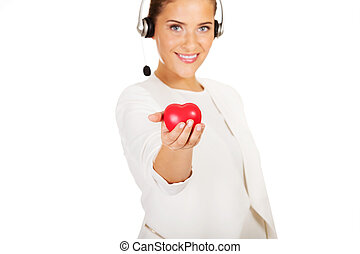 Happy call center woman with heart toy