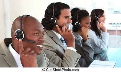 Happy call centre agents talking with their headsets in a...