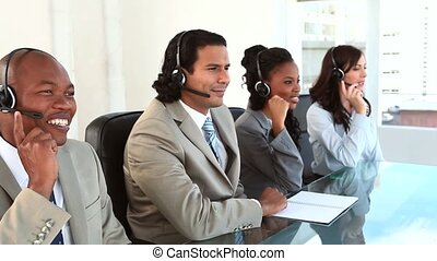 Happy call centre agents working with headsets in a bright...
