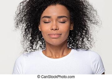 Happy calm african woman taking deep breath of fresh air
