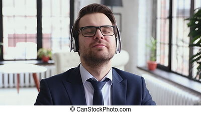 Happy calm professional businessman listening to chill music with serene face eyes closed at work. Carefree ceo wearing suit, wireless headphones enjoying stress free break time relaxing in office.