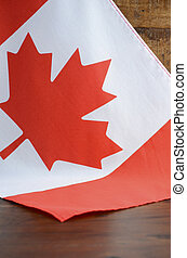 Canadian red and white maple leaf flag against dark wood rustic background for Canada Day, July 1, celebration and national holidays.