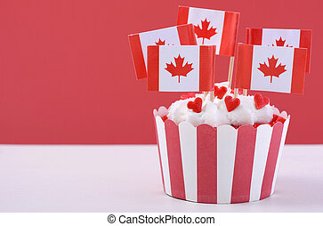 Happy Canada Day Party Cupcake with maple leaf flags on a white wood table against a red background.