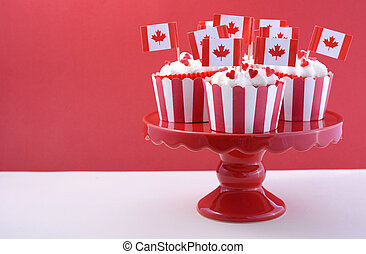 Happy Canada Day Party Cupcakes on a red cake stand with maple leaf flags on a white wood table and red background.
