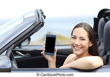 Happy car driver showing blank phone screen