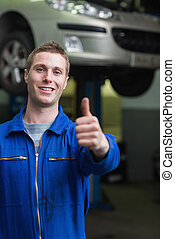 Happy car mechanic gesturing thumbs up
