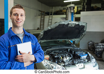 Happy car mechanic with tablet pc