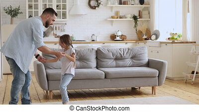 Happy carefree active family having fun together at home.