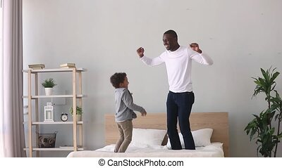 Happy carefree african father and kid son jumping on bed