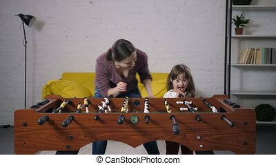 Happy carefree family playing table soccer at home
