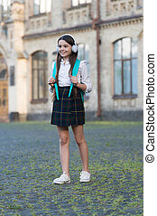 Happy carefree girl child back to school listening music, formal education concept.