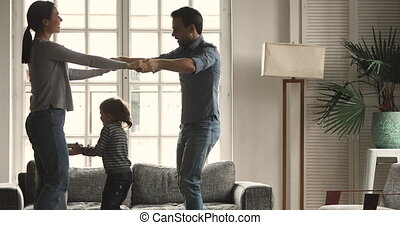 Happy carefree parents and kids enjoying dancing together at home