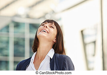 Happy carefree woman laughing outside in city