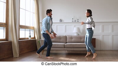 Happy carefree young couple dancing in living room together