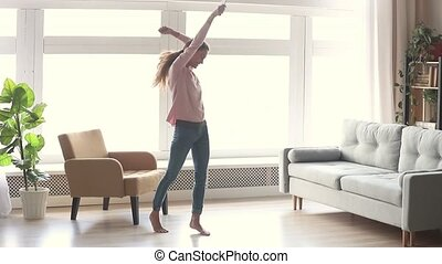 Happy carefree young woman dancing listen to music on smartphone