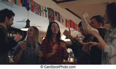 Happy careless students in casual clothes are dancing in...