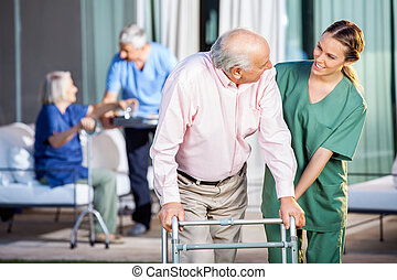 Happy Caretaker Assisting Senior Man In Using Zimmer Frame