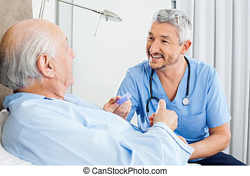 Happy male caretaker discussing prescription medicine with senior man in bedroom at nursing home