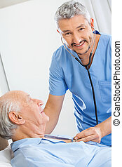 Happy Caretaker Examining Senior Man With Stethoscope