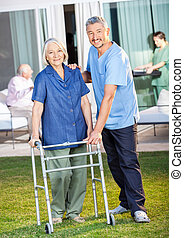 Portrait of happy caretaker helping senior woman to use Zimmer frame at nursing home lawn