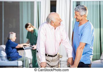 Happy Caretaker With Disabled Senior Man At Yard