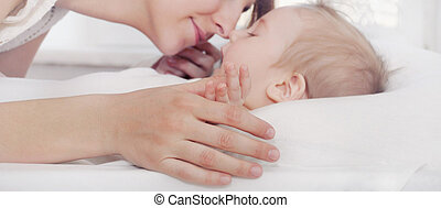 happy caring mother holding little fingers of her cute baby boy