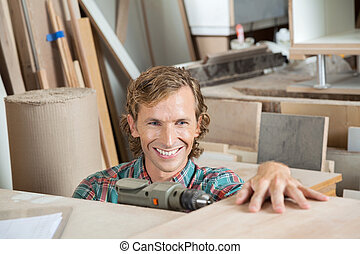 Happy Carpenter Drilling Wood In Workshop