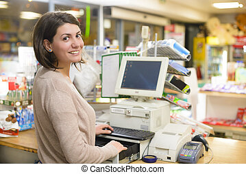 Happy Cashier - Young woman at cash register in a store