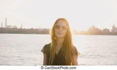 Happy casual Caucasian girl in fashionable sunglasses posing...