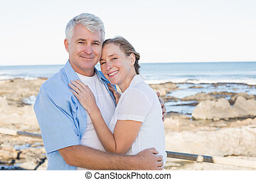 Happy casual couple embracing by the sea