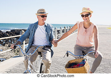 Happy casual couple going for a bike ride on the pier on a ...