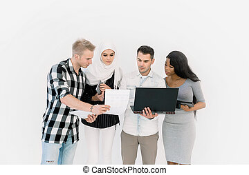 Happy Casual Group Of Four Multiethnic People Standing Over White Background, using laptop and tablets while working together. Study, business, education concept