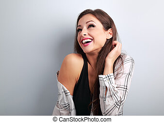 Happy casual toothy laughing woman in shirt looking up on blue background