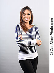 Happy casual toothy smiling woman with folded arms looking on empty copy space background.