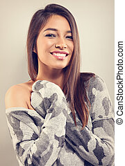 Happy casual toothy wide smiling woman in grey winter warm sweater looking on empty copy space background. Closeup portrait. Toned