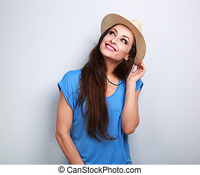 Happy casual woman in summer hat thinking about vacation and looking up on blue background