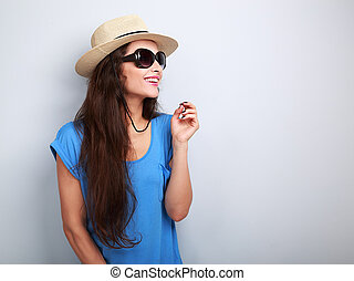 Happy casual woman in sun glasses and hat looking up on blue background with empty copy space