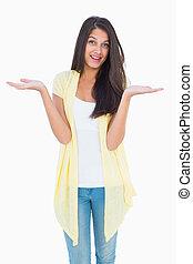 Happy casual woman shrugging her shoulders