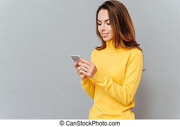 Happy casual woman using smartphone