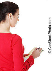 Happy casual woman writing on a piece of paper. Back view.